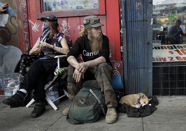 In this Oct. 1, 2018 photo, Stormy Nichole Day, left, sits on a sidewalk on Haight Street with Nord (last name not given) and his dog Hobo while interviewed about being homeless in San Francisco