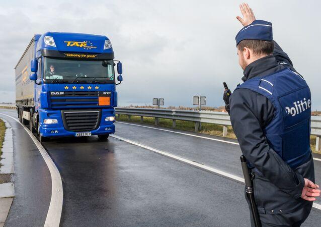 A police man stops a truck on the French-Belgian border in Adinkerke, Belgium, on Wednesday, Feb. 24, 2016.