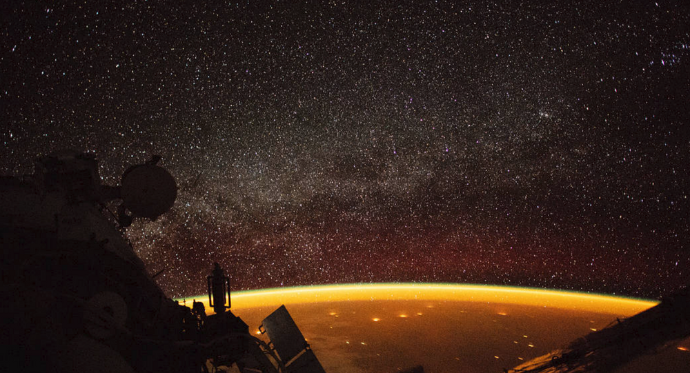 Astronaut aboard the International Space Station captures image of orange airglow enveloping Earth