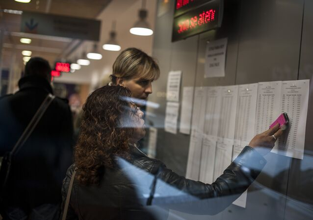 A woman looks at a list inside a state unemployment office, in Pamplona northern Spain on Thursday, Jan. 23, 2014.