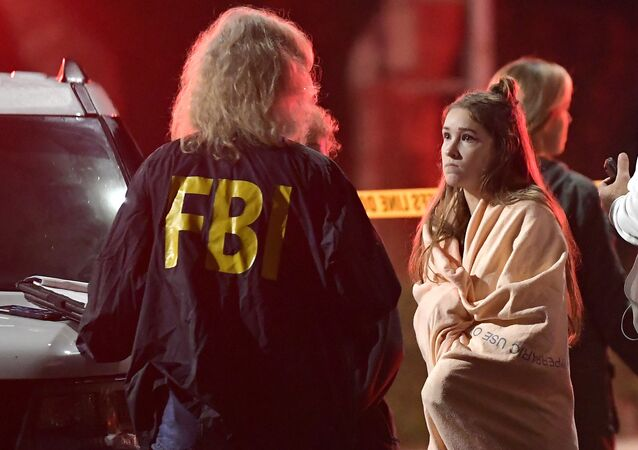 An FBI agent talks to a potential witness as they stand near the scene Thursday, Nov. 8, 2018, in Thousand Oaks, Calif. where a gunman opened fire Wednesday inside a country dance bar crowded with hundreds of people on college night, wounding 11 people including a deputy who rushed to the scene