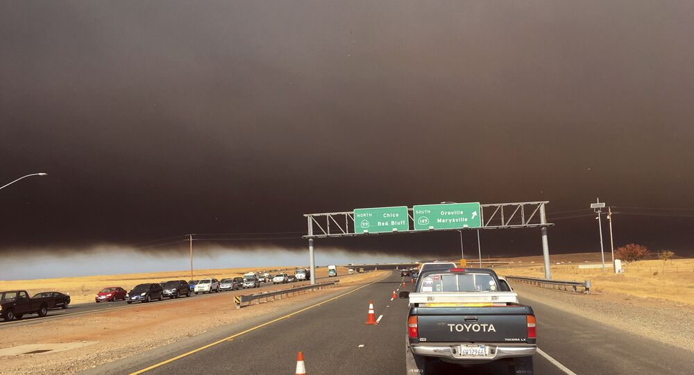 Smoke from the Camp Fire, burning in the Feather River Canyon near Paradise, Calif., darkens the sky as seen from Highway 99 near Marysville, Calif., Thursday, Nov. 8, 2018.