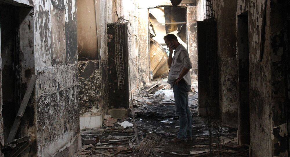 In this Friday, Oct. 16, 2015 photo, an employee of Doctors Without Borders walks inside the charred remains of their hospital after it was hit by a U.S. airstrike in Kunduz, Afghanistan