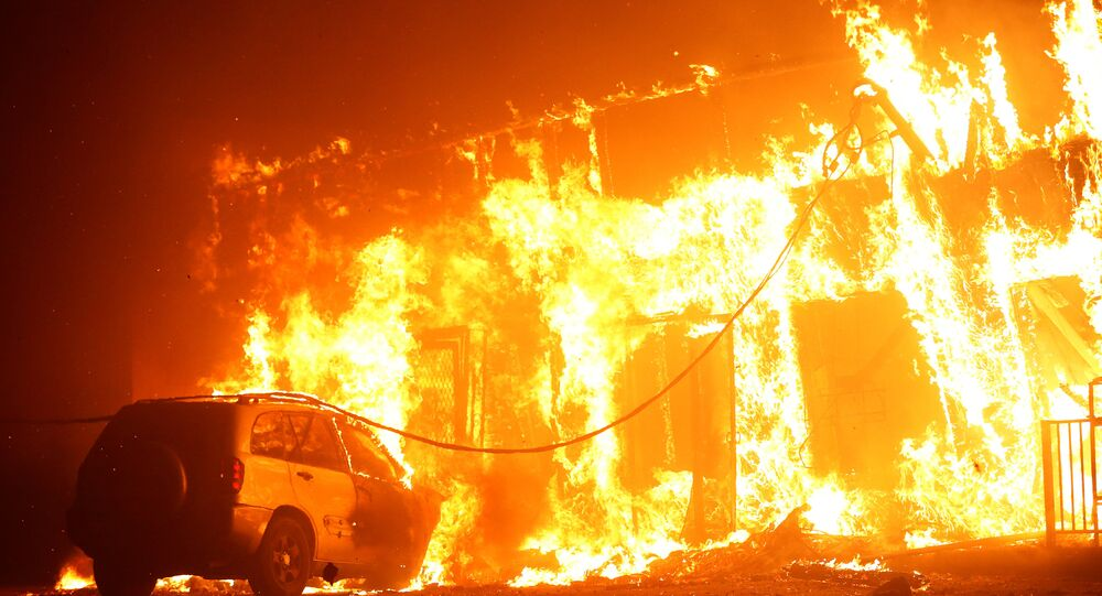 A structure is seen engulfed in flames during the Camp Fire in Paradise