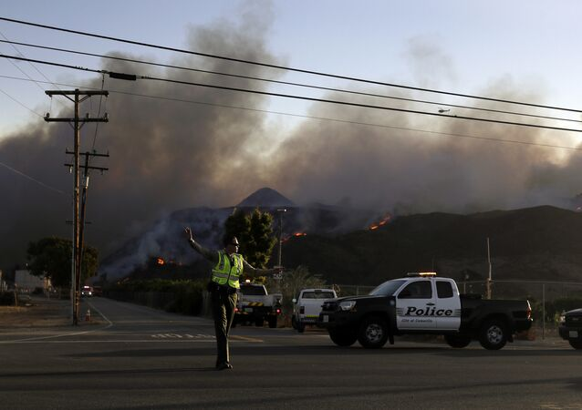 A police officer mans a checkpoint in front of an advancing wildfire Thursday, Nov. 8, 2018, near Newbury Park, Calif. The Ventura County Fire Department has also ordered evacuation of some communities in the path of the fire, which erupted a few miles from the site of Wednesday night's deadly mass shooting at a Thousand Oaks bar.