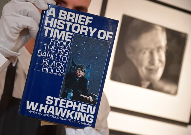 Fine-art handler Tom Richardson poses with a copy of A Brief History of Time which, has a thumb-print inside by author British theoretical physicist Stephen Hawking, ahead of an auction of items from Hawkinsg' personal estate at Christie's in London, Britain October 30, 2018.