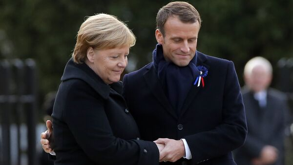 French President Emmanuel Macron, right, holds the hands of German Chancellor Angela Merkel during a ceremony in Compiegne, north of Paris, Saturday, Nov. 10, 2018. - Sputnik International