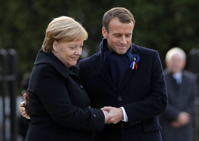 French President Emmanuel Macron, right, holds the hands of German Chancellor Angela Merkel during a ceremony in Compiegne, north of Paris, Saturday, Nov. 10, 2018.