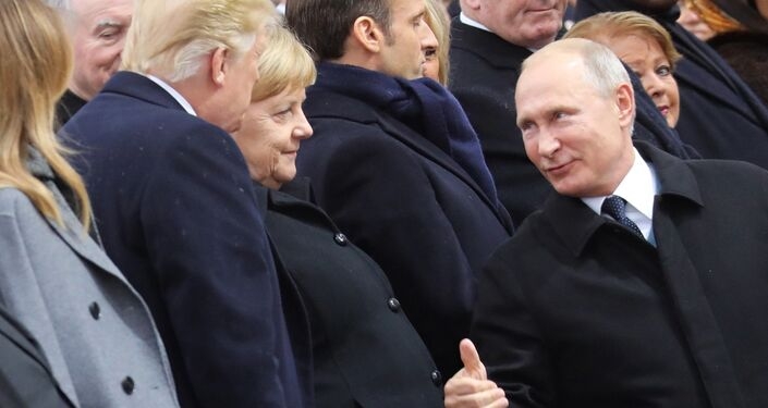 Russian President Vladimir Putin talks with German Chancellor Angela Merkel and US President Donald Trump as they attend a ceremony at the Arc de Triomphe in Paris, as part of commemorations marking the 100th anniversary of the 11 November 1918 armistice, ending World War I, Sunday, Nov. 11, 2018.