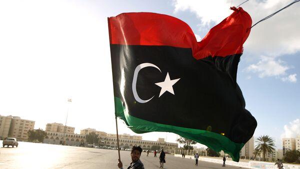 A Libyan man waves a national flag - Sputnik International