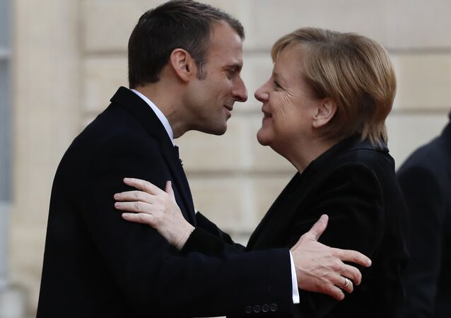 French President Emmanuel Macron hugs German Chancellor Angela Merkel in the courtyard of the Elysee Palace Sunday, Nov. 11, 2018 in Paris