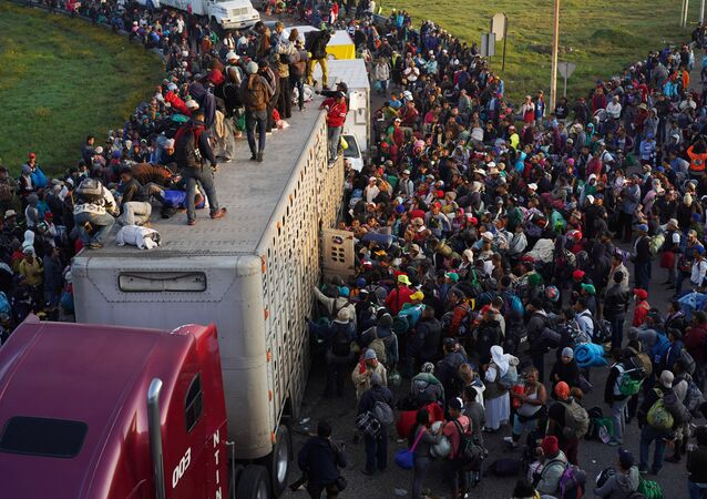 Migrants, part of a caravan of thousands traveling from Central America en route to the United States, try to catch a ride on a truck, in Irapuato, Mexico November 12, 2018