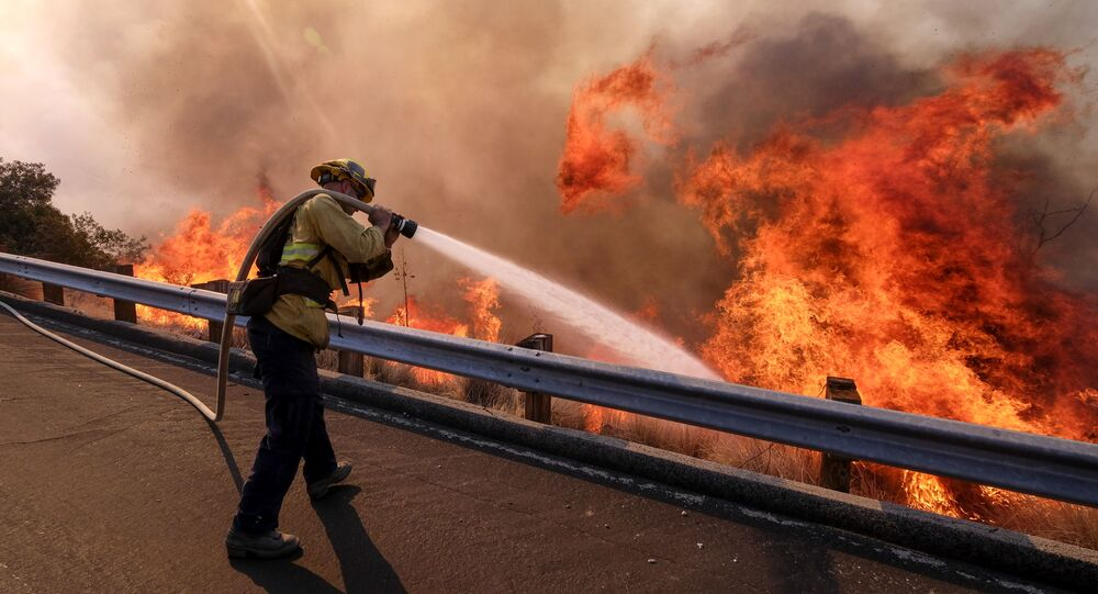 A firefighter battles a fire along the Ronald Reagan Freeway, aka state Highway 118, in Simi Valley, Calif., Monday, Nov. 12, 2018