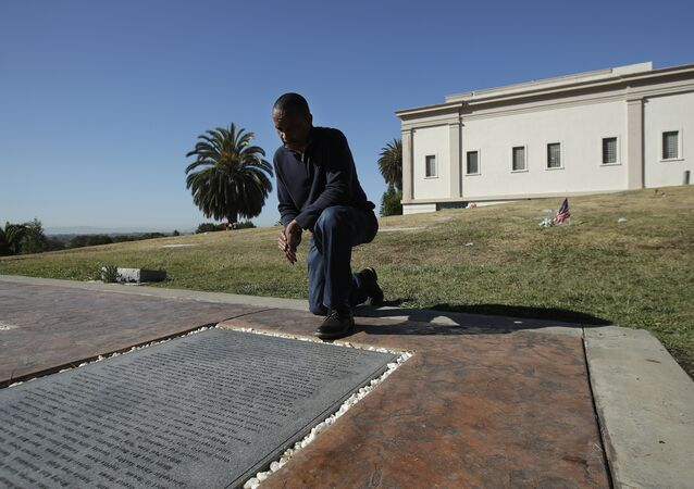 John Cobb looks at names of his relatives on the Jonestown Memorial in Oakland, California.