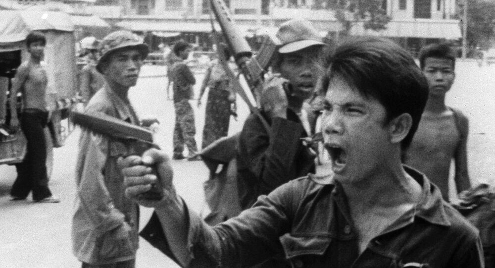 FILE - In this 17 April 1975 file photo, a Khmer Rouge soldier waves his pistol and orders store owners to abandon their shops in Phnom Penh, Cambodia as the capital fell to the communist forces