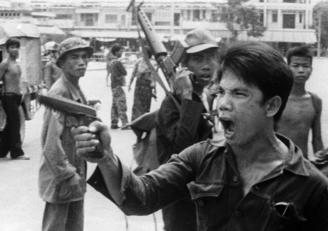 FILE - In this April 17, 1975 , file photo, a Khmer Rouge soldier waves his pistol and orders store owners to abandon their shops in Phnom Penh, Cambodia on as the capital fell to the communist forces