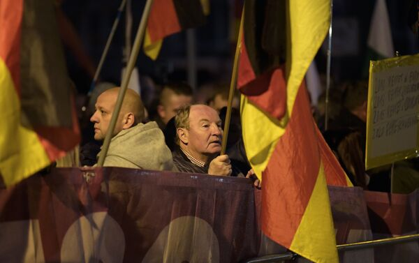Demonstrators with German flags attend a protest against the visit of German Chancellor Angela Merkel at the East German city Chemnitz on Friday, Nov. 16, 2018. - Sputnik International