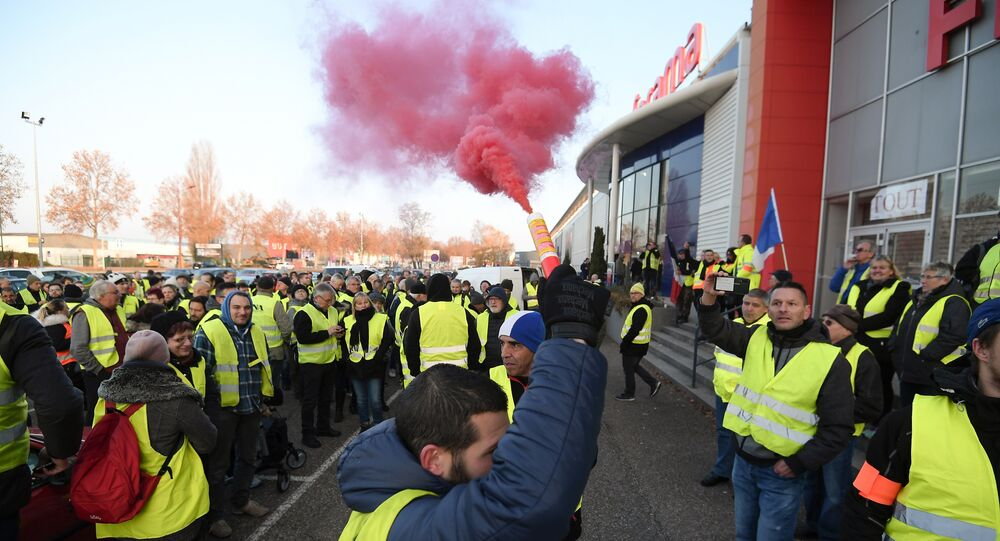 A demonstrators holds a flare during a demonstration of Yellow Vests (Gilets jaunes) against the rising of the fuel and oil prices on November 17, 2018 in Vendenheim, eastern France.
