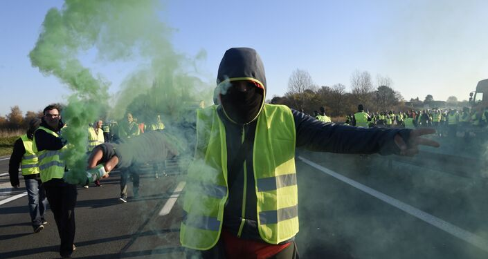 A man holds a flare as demonstrators wearing yellow vests (Gilets jaunes) protest against the rising of the fuel and oil prices on November 17, 2018 in Haulchien near Valenciennes, northern France.