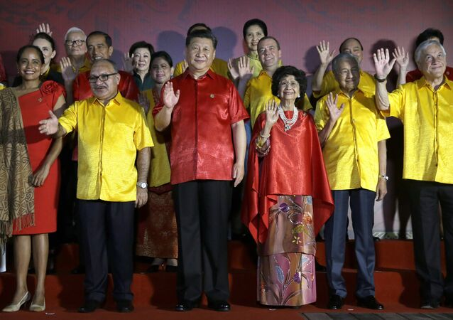 Leaders and their spouses including, from second left, Papua New Guinea's Prime Minister Peter O'Neill, Chinese President Xi Jinping, Malaysian Prime Minister Mahathir Mohamad and his wife Siti Hasmah Mohamad Ali, and Chile's President Sebastian Pinera wave during a family photo with leaders and their spouses during the APEC Economic Leaders Meeting summit in Port Moresby, Papua New Guinea, Saturday, Nov. 17, 2018