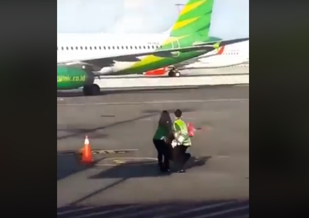 Woman chases plane on the runway before being tackled to the ground by staff in Bali