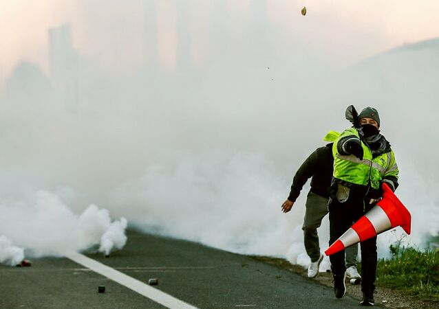 A man throws a projectile on Caen's circular road on November 18, 2018 in Caen, northwestern France, on a second day of action after a nationwide popular initiated day of protest called yellow vest (Gilets Jaunes in French) movement against high fuel prices which has mushroomed into a widespread protest against stagnant spending power under French President.