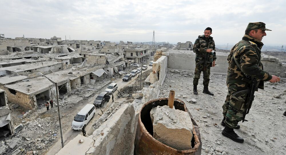Forces loyal to Syria's President Bashar al-Assad stand atop of a building in the government held Sheikh Saeed district of Aleppo, during a media tour, Syria