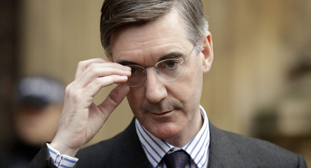 Pro-Brexit, Conservative lawmaker Jacob Rees-Mogg adjusts his glasses as he speaks to the media outside the Houses of Parliament in London, Thursday, Nov. 15, 2018.