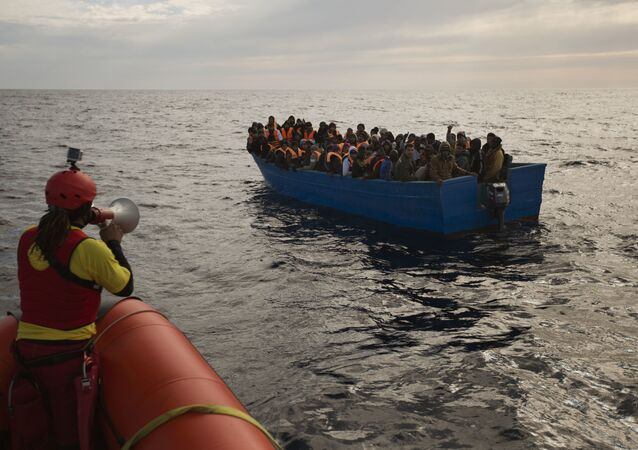 Migrants and refugees are assisted by members of the Spanish NGO Proactiva Open Arms, as they crowd aboard a boat sailing out of control in the Mediterranean Sea about 21 miles north of Sabratha, Libya, on Friday, Feb. 3, 2017. European Union leaders are poised to take a big step on Friday in closing off the illegal migration routes from Libya across the central Mediterranean, where thousands have died trying to reach the EU, the EU foreign affairs chief Federica Mogherini said.