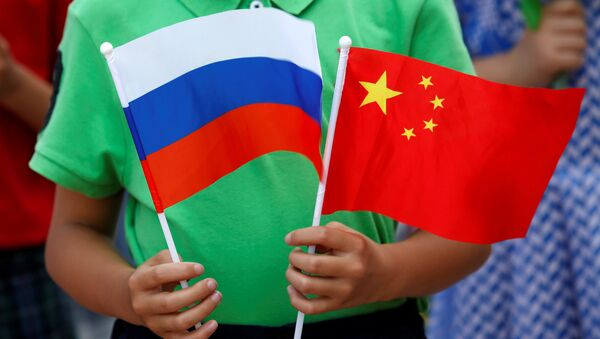 A child holds the national flags of Russia and China prior to a welcoming ceremony for Russian President Vladimir Putin outside the Great Hall of the People in Beijing, China, June 25, 2016 - Sputnik International