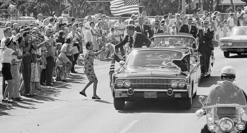 A woman runs into the street and tosses President John Kennedy a floral lei, which he caught,during a motorcade through Honolulu June 9, 1963 from the Pearl Harbor Naval Base to a Waikiki Beach Hotel where he made a strong plea for civil rights before a conference of the nation's mayors