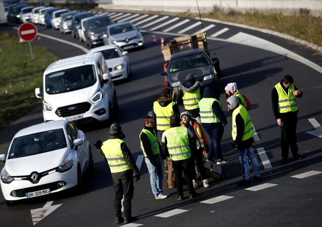 Protesters wearing yellow vests, a symbol of a French drivers' protest against higher fuel prices, attend a demonstration at the entrance of a shopping center in Nantes, France, November 19, 2018