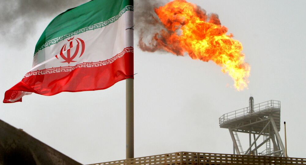 A gas flare on an oil production platform in the Soroush oil fields seen alongside an Iranian flag
