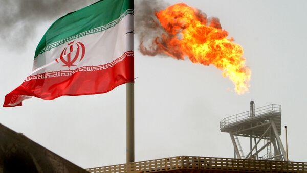 A gas flare on an oil production platform in the Soroush oil fields seen alongside an Iranian flag - Sputnik International