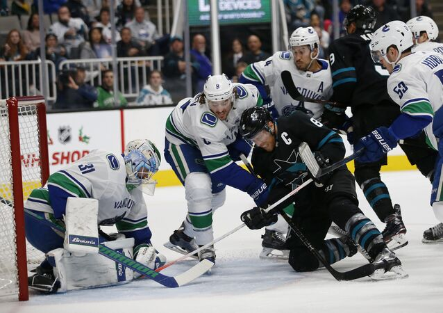Vancouver Canucks' Anders Nilsson (31) makes a save against San Jose Sharks' Joe Pavelski (8) with the help of Canucks' Christopher Tanev (8) and Michael Del Zotto (4) during the first period of an NHL hockey game in San Jose, Calif., Friday, Nov. 23, 2018