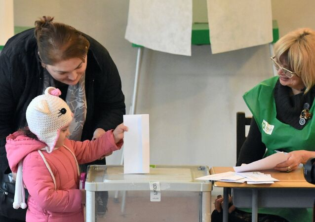 A girl puts the ballot in the ballot box at one of the polling stations in Tbilisi.