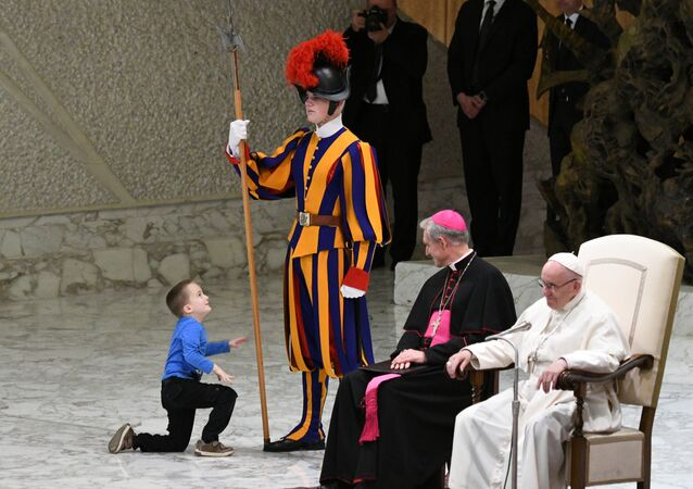 Prefect of the Papal Household, Georg Ganswein (C) watches a boy who came from the audience onto the stage, play with a Swiss Guard's spear as Pope Francis (R) looks on during the weekly general audience on November 28, 2018 in Paul VI hall at the Vatican.