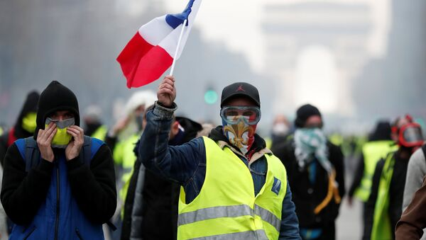 Masked protesters wearing yellow vests, a symbol of a French drivers' protest against higher fuel prices, take part in a demonstration on the Champs-Elysees in Paris, France, November 24, 2018 - Sputnik International