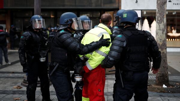 French riot police apprehend a protester wearing a yellow vest, a symbol of a French drivers' protest against higher fuel prices, during clashes on the Champs-Elysees in Paris, France, November 24, 2018. Picture taken November 24, 2018 - Sputnik International