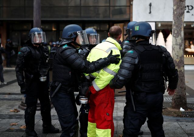 French riot police apprehend a protester wearing a yellow vest, a symbol of a French drivers' protest against higher fuel prices, during clashes on the Champs-Elysees in Paris, France, November 24, 2018. Picture taken November 24, 2018