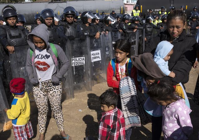 Migrants stand near Mexican police at the Mexico-U.S. border in Tijuana, Mexico, Sunday, Nov. 25, 2018, as they try to reach the US.