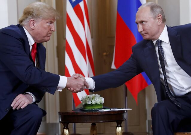 In this file photo taken on 16 July 2018, US President Donald Trump and Russian President Vladimir Putin shake hands at the beginning of a meeting at the Presidential Palace in Helsinki, Finland.