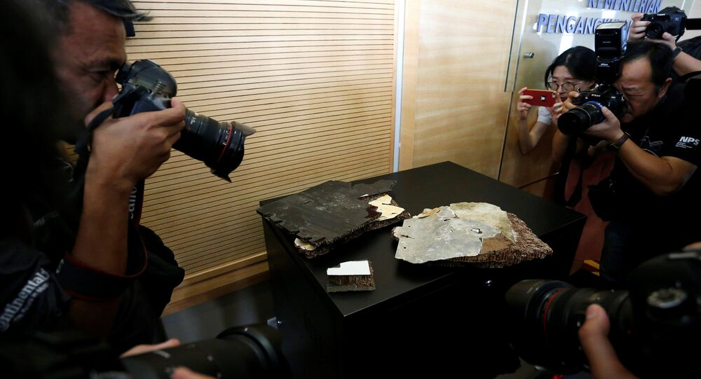 Photographers take photos of debris believed to belong to the missing Malaysia Airlines MH370, in Putrajaya, Malaysia November 30, 2018