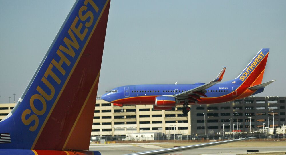 In this Feb. 9, 2012, a Southwest Airlines Boeing lands at Chicago's Midway Airport as another sits at a gate. Southwest Airlines Co. said Thursday, March 1, 2012, that it took a step toward combining its fleet with that of AirTran Airways as U.S. officials gave the airlines a single operating certificate
