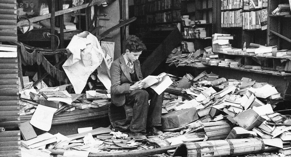 a boy sits amid the ruins of a London bookshop following an air raid on Oct. 8, 1940