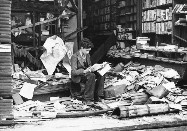 a boy sits amid the ruins of a London bookshop following an air raid on Oct. 8, 1940