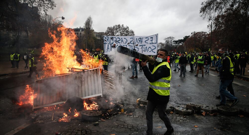 Protesters build a barricade during a protest of Yellow vests (Gilets jaunes) against rising oil prices and living costs, on December 1, 2018 in Paris