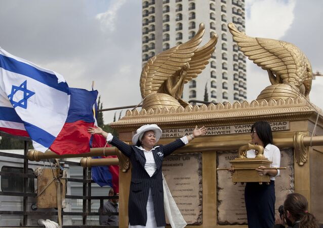 Grace Galindez-Gupana, left, a businesswoman from the Philippines, stands next to what she says is the world's largest model of the Ark of the Covenant, the biblical chest which was said to have held the Ten Commandments in Jerusalem, Tuesday, Sept. 24, 2013.