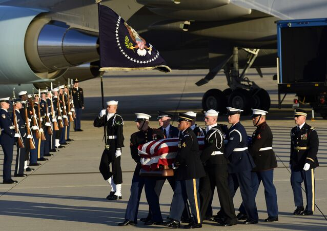 Casket of former President George H.W. Bush is carried by a joint services military honor guard to a hearse at Andrews Air Force Base in Maryland