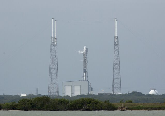 An unmanned SpaceX Falcon 9 rocket with a Dragon capsule sits on launch pad 40 after a scrubbed launch attempt